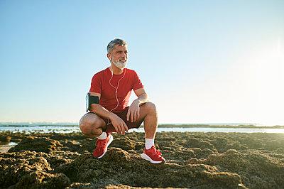 Man crouching on rocks at beach - p300m2275613 by Kiko Jimenez