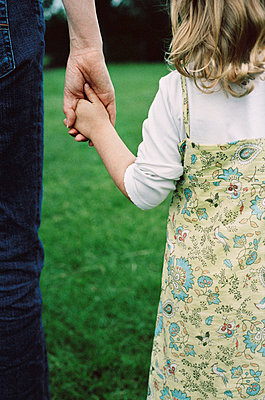 Rear view of young girl holding mothers hand - p349m695139 by Emma Lee