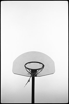 Basketball hoop with tattered net hanging from rim - p3720296 by James Godman