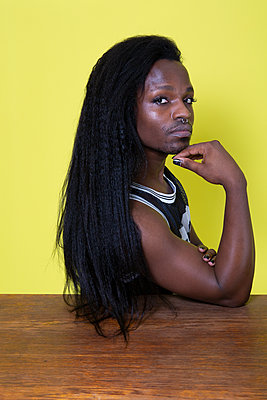 Dark-skinned man with long hair, portrait - p817m2203223 by Daniel K Schweitzer