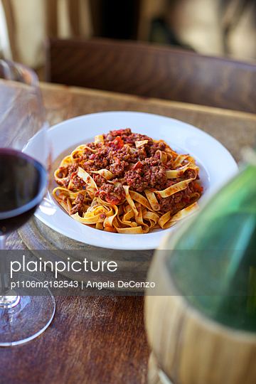 A plate of Tagliatelle alla Bolognese and a glass of red wine.  - p1106m2182543 by Angela DeCenzo