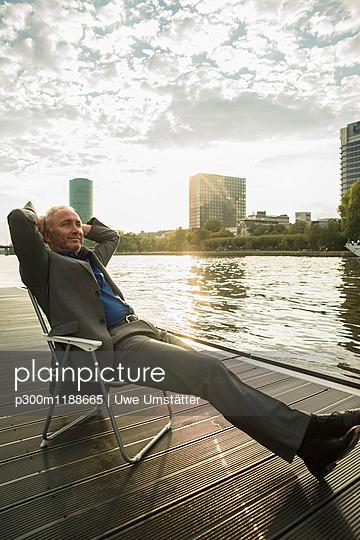 Germany, Frankfurt, relaxed businessman at river Main