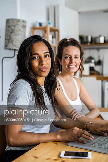 Portrait of two smiling women sitting with laptop at table at home - p300m2080151 by Giorgio Fochesato