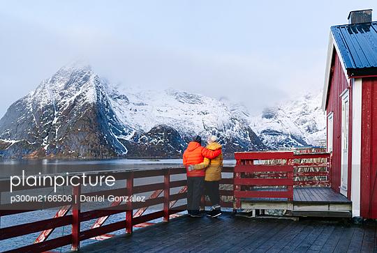 Tourist couple enjoying the view at Hamnoy, Lofoten, Norway - p300m2166506 by Daniel González
