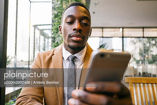 Young businessman using smartphone in a cafe - p300m2202408 by Andrés Benitez