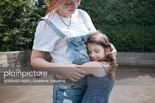 Daughter hugging mother on basketball court at back yard - p300m2214020 by Ekaterina Yakunina