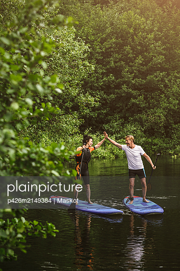 Senior woman and man high-fiving while learning paddleboarding in sea during SUP course - p426m2149384 by Maskot