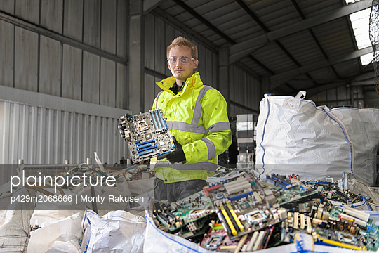 Worker sorting out old circuit boards for recycling in recycling factory - p429m2068666 by Monty Rakusen