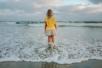 Rear view of girl standing in sea at beach - p1166m1509165 by Cavan Images