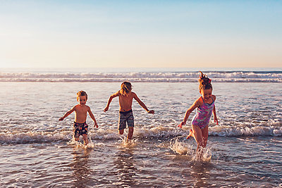 Three little kids running in the water at the beach - p1166m2247145 by Cavan Images