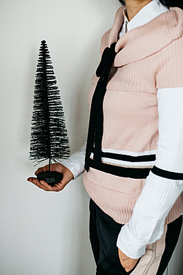 Woman holding artificial Christmas tree in her hand - p1621m2231149 by Anke Doerschlen