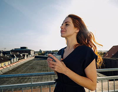 Smiling redheaded woman having a coffee break on rooftop terrace - p300m2167256 von Kniel Synnatzschke