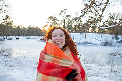 Cheerful redhead woman wrapped in blanket during winter at sunset - p300m2287410 by Frank van Delft