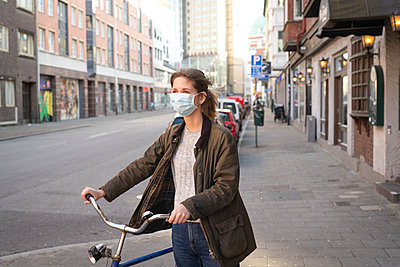 Woman with bicycle wearing face mask - p312m2191615 by Viktor Holm