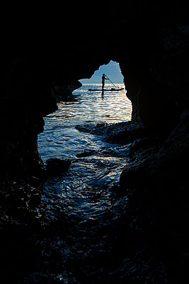 Man paddleboarding in sea, Misool, Raja Ampat, Indonesia - p343m2025663 by Ryan Salm Photography