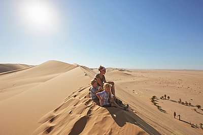 Mother and sons sitting on sand dune, Dune 7, Namib-Naukluft National Park, Africa - p429m1029880 by Stephen Lux