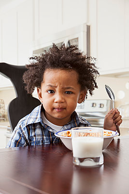 Mixed race boy eating at table - p555m1464119 by Mike Kemp