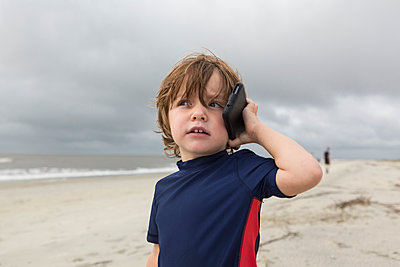 Caucasian boy talking on cell phone on beach - p555m1522943 by Marc Romanelli