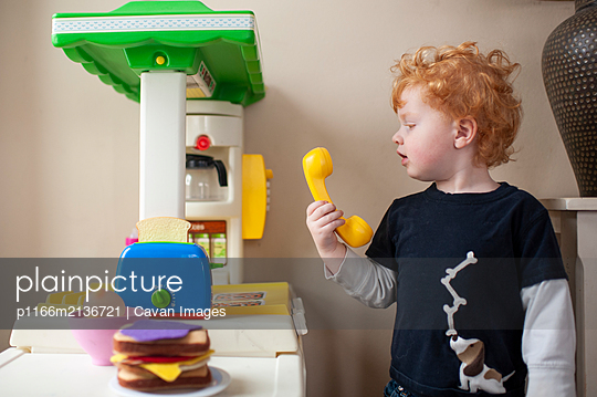 Toddler looking at phone in play kitchen with cute expression at home - p1166m2136721 by Cavan Images