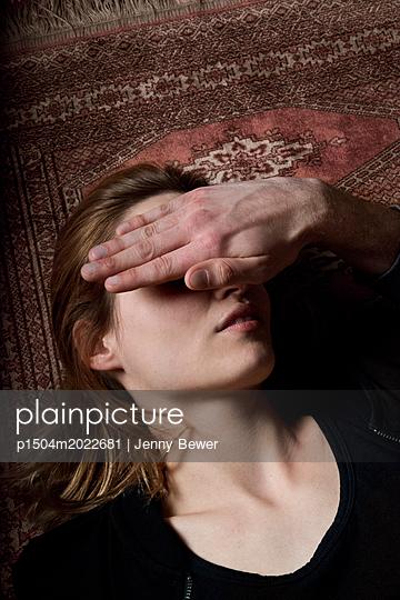 Hand verdeckt das Gesicht einer Frau die am Boden liegt - p1504m2022681 von Jenny Bewer