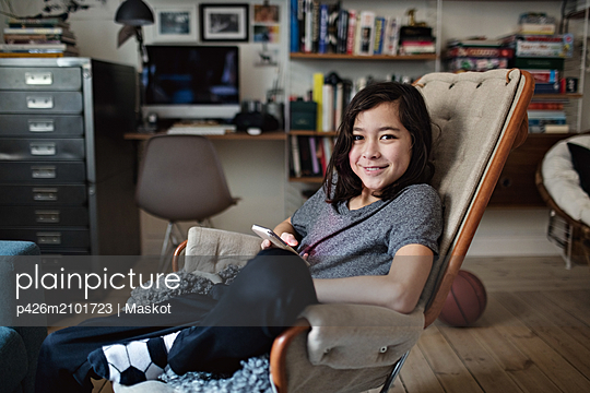 Portrait of smiling boy with long hair using social media at home - p426m2101723 by Maskot