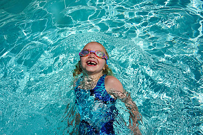High angle view of happy girl swimming in pool at tourist resort during sunny day - p1166m2105971 by Cavan Images
