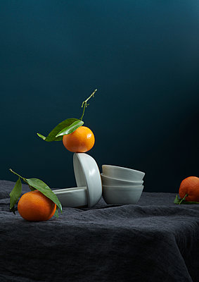 Oranges and dishes on a table - p1629m2211341 by martinameier