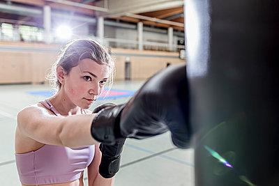 Female boxer practising at punchbag in sports hall - p300m2144495 von Stefanie Baum