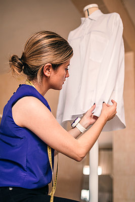 Female fashion designer examining shirt on dressmaker's model at workshop - p300m2293505 by LUPE RODRIGUEZ