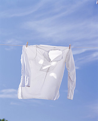 Low angle view of a shirt hanging on a clothesline - p3485441 by Björn Andrén