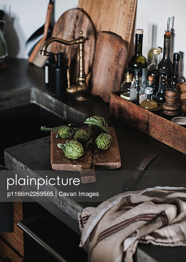 Fresh green baby artichokes on wooden cutting board in the kitchen - p1166m2269565 by Cavan Images