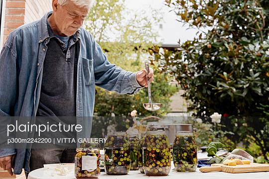Senior man preparing olives in jars on table at back yard - p300m2242200 by VITTA GALLERY