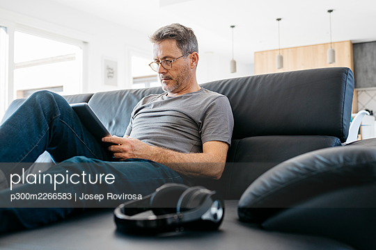 Mature man using digital tablet while sitting on sofa in living room - p300m2266583 by Josep Rovirosa