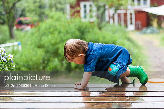 Toddler on patio in rain - p312m2086364 by Anne Dillner