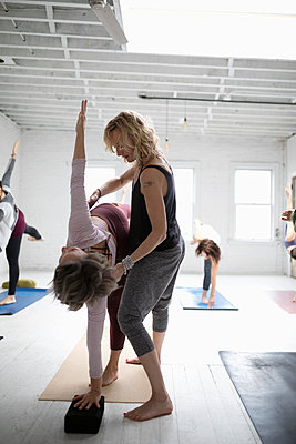 Yoga instructor helping woman practicing half moon pose in yoga class - p1192m1583337 by Hero Images
