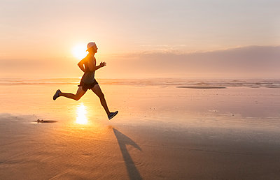 Man running on the beach at sunset - p300m1166692 by Marco Govel