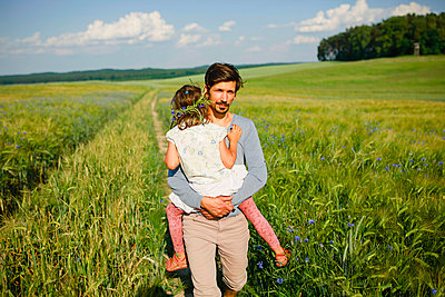 Portrait father carrying daughter in sunny, idyllic rural field - p301m2075818 by Sven Hagolani