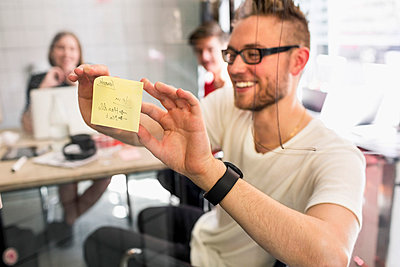 Young businessman sticking adhesive note on transparent glass with colleagues at background in new office - p426m927760f by Maskot