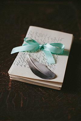 Feder auf einem Stapel alter Briefe - p946m956190 von Maren Becker