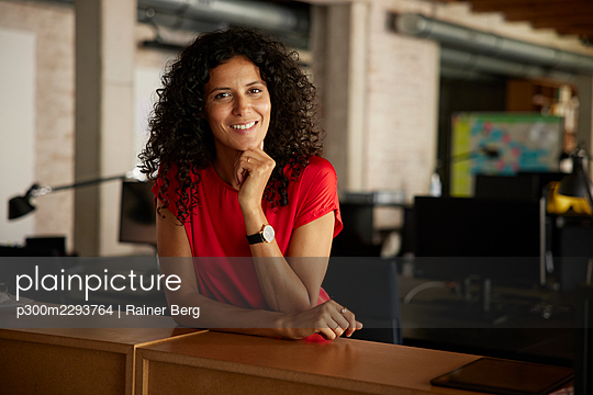 Smiling businesswoman with hand on chin leaning at workplace - p300m2293764 by Rainer Berg