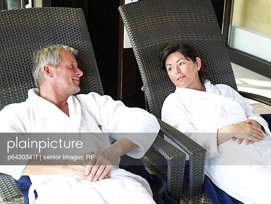Aelteres Paar sitzt in weissen Bademaenteln auf Liegestuehlen  - p6430341f von senior images RF