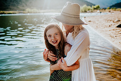 Mom and Daughter hugging and smiling while standing in a lake - p1166m2208017 by Cavan Images