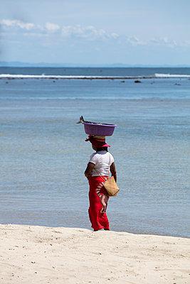 Frau mit Fischfang am Strand - p1272m1515609 von Steffen Scheyhing