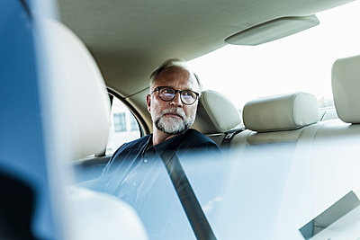 Mature businessman sitting on backseat in car, looking out of window - p300m2023688 von Uwe Umstätter