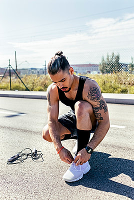 Sporty young man tying shoes before training on a road - p300m2140626 by Marco Govel