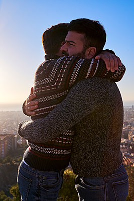 Loving gay men embracing while standing against clear sky during sunrise, Bunkers del Carmel, Barcelona, Spain - p300m2257349 by Veam