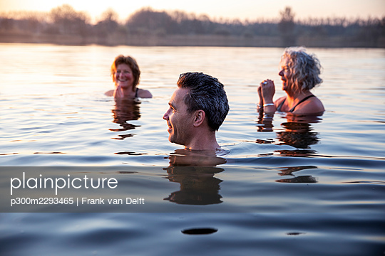 Smiling man looking away while female friends with hands clasped enjoying cold water during morning - p300m2293465 by Frank van Delft