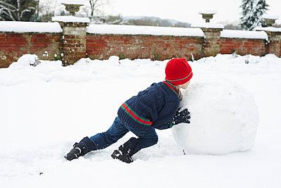 Boy making snowman outdoors - p1023m805991f by Paul Viant