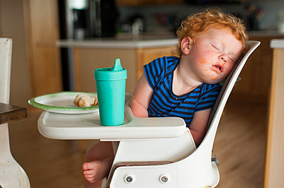 Close-up of cute baby boy with food and drink sleeping on high chair at home - p1166m2105834 by Cavan Images