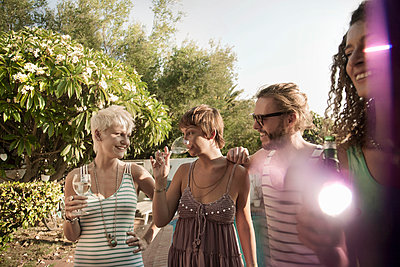 Smiling women and man enjoying party while drinking outdoors - p300m2220509 by LOUIS CHRISTIAN